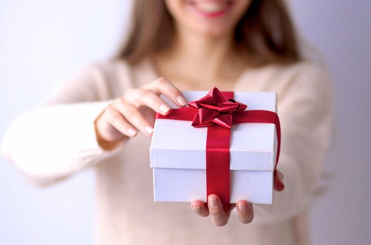 Dia das Mães - Mulher com presente na mão, em caixa branca e fita vermelha - Agência 3GRAUS