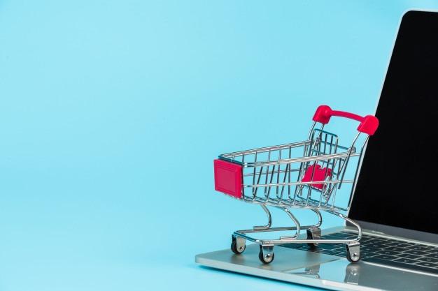 Remarketing - Carrinho de compras em cima do computador, em fundo azul - Agência 3GRAUS